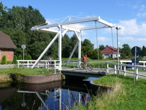 Cyclist on a marshland bridge in Ostrhauderfehn