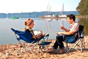 Relaxed couple on the beach with rowing and sailing boats on the lake