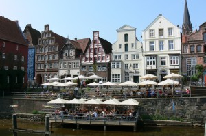 Old buildings in the town of Lüneburg can be seen in the background with the river on which it stands in the foreground. Lots of people are sitting at restaurant tables in the street between the buildings and by the river.