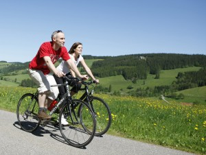 Two cyclists on the Southern Black Forest Cycle Route with Black Forest scenery in summer