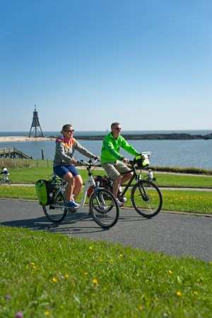 Couple cycling at the Kugelbake beacon, Cuxhaven