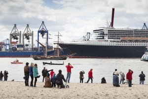 Hamburg: Queen Mary II cruise liner, spectators on the Elbe river bank in Oevelgoenne