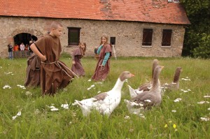 Children dressed as monks with abbey geese in front of the tithe barn
